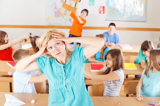 "Uncontrollable pupils in classroom acting out, frustrated teacher ""tearing her hair out""."