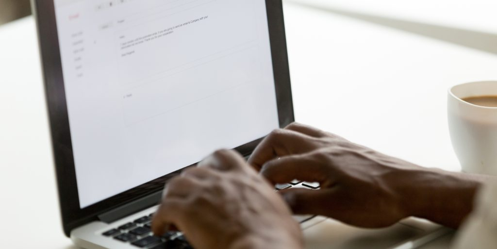 African american businessman typing e-mail on laptop using online application