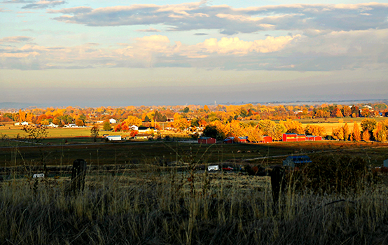 Morning sun glowing on a small country town with red barns and farm lands. Trees are in beautiful yellow and orange Autumn colors. This image gives a peaceful quiet country feel.